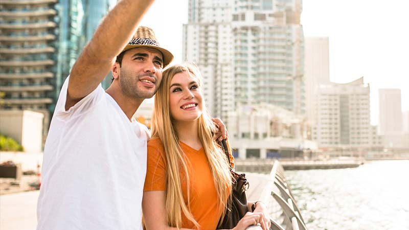 A young couple sightsee on a walkway near the marina in Dubai.