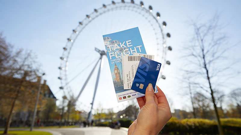A hand holding a London Eye pamphlet, tickets, and a Visa card with the London Eye in the background.