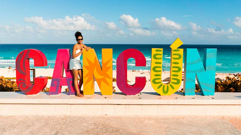 Woman posing next to a sign that reads 'Cancun'.