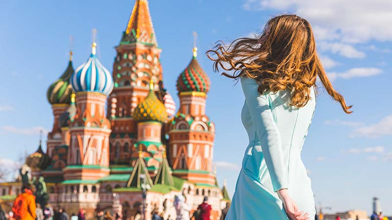A woman walks towards St. Basil's cathedral in Moscow, Russia.