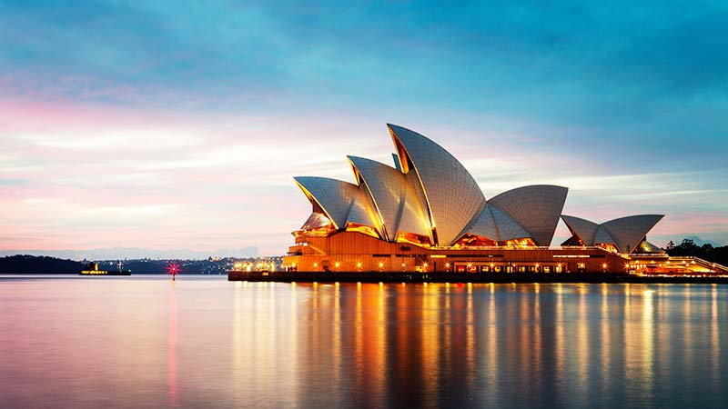 The Sydney Opera House, glittering with lights, at dusk.