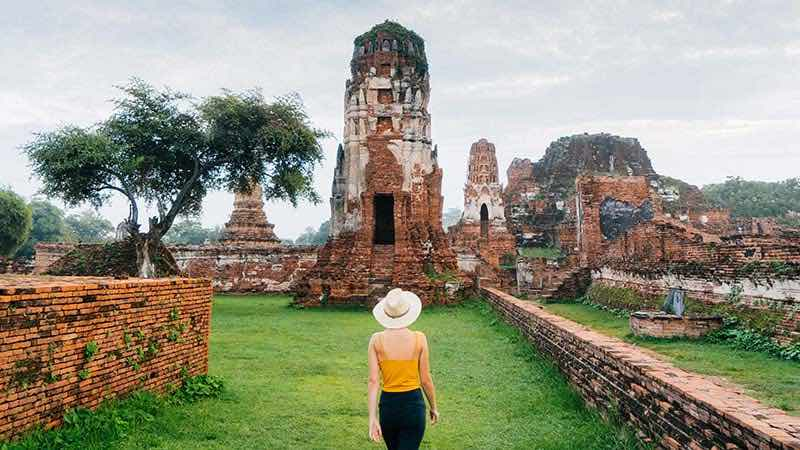 A female tourist explores a historical site in Thailand.