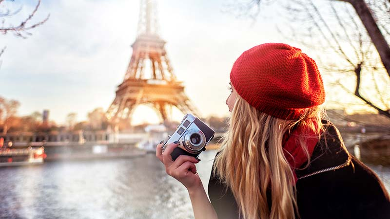 A young woman holding a camera in front of the Eiffel Tower in Paris.