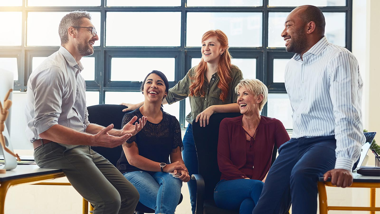 Group of five professional men and women talking and laughing.