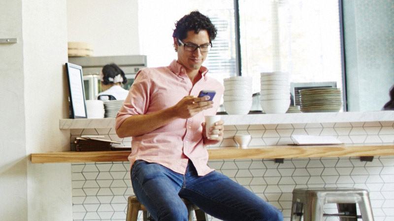 Man sitting at counter looking at mobile phone and holding a cup of coffee.